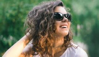 Modelo con pelo castaño enrulado con anteojos de sol, sonriendo.