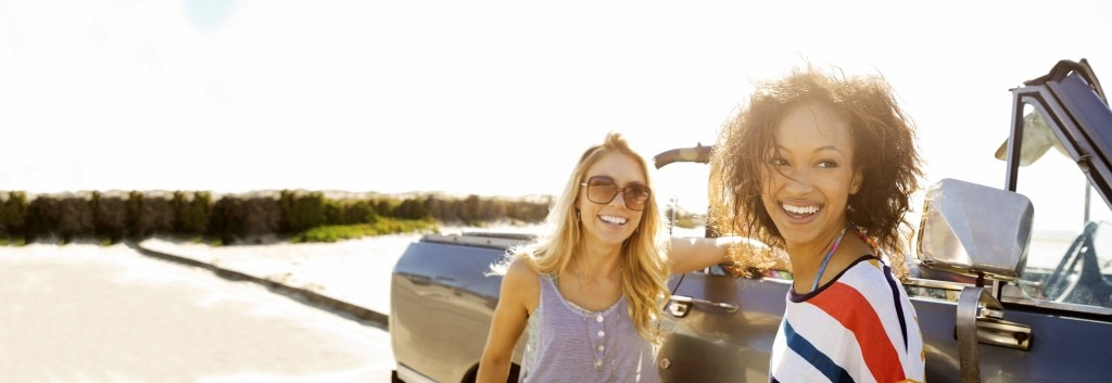 Two women smiling, one with smooth dry hair and the other with curly dry hair, near a car.