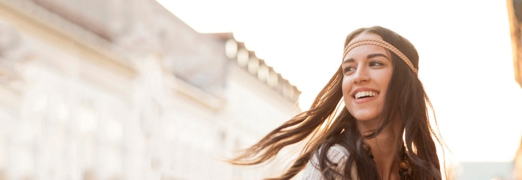 Primer plano de una mujer sonriendo con pelo castaño graso, con una blusa beige, parada en la calle.